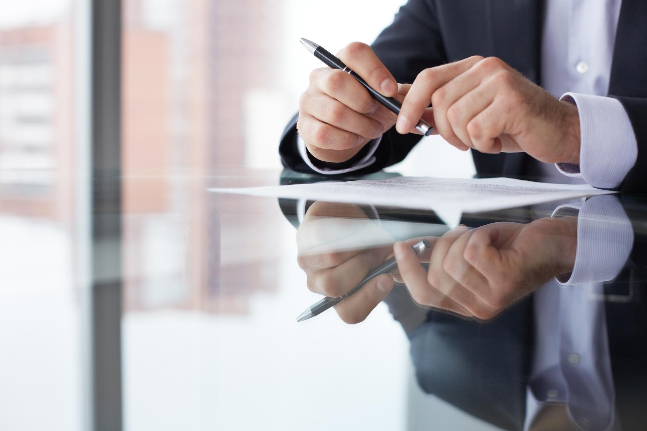 Businessman holding a pen over a document